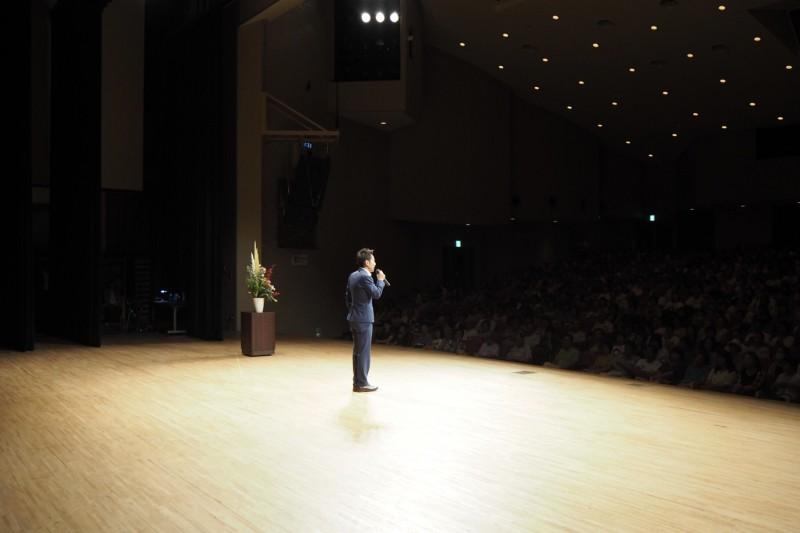 講演会 舞台で話す男性 後ろ姿