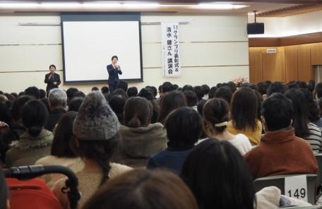 講演会 舞台で話す男性 話を聞く人々
