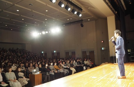舞台で話す男性 講演会 話を聞く人々